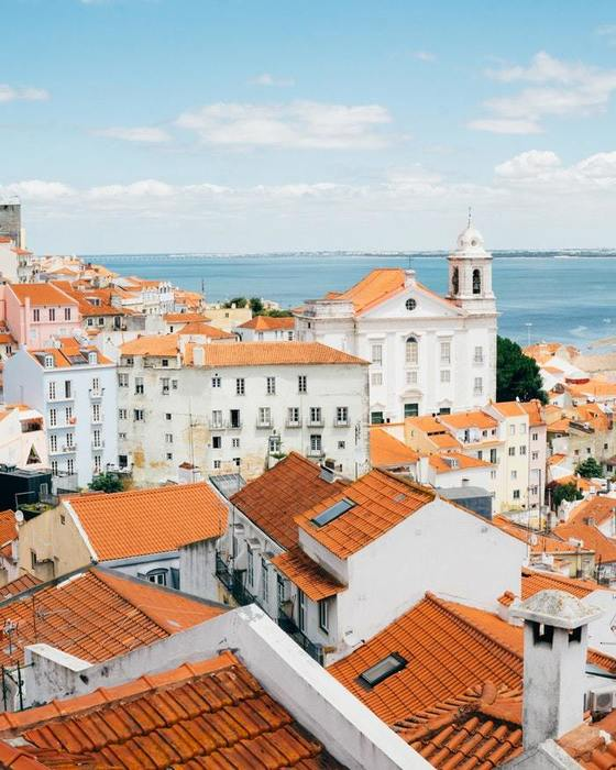 Lisbon, Portugal. Tall residential buildings painted white with orange clay roof tiles. Ocean in the background.