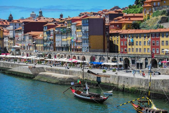Portugal. Ship at port. Stone commercial buildings. Tall, colorful residential buildings with orange, clay tile roofing.